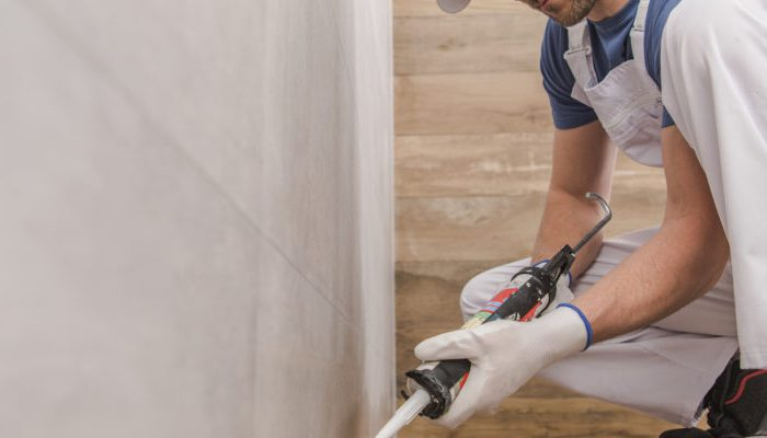 Finishing Bathroom Remodeling. Using Silicone to Seal Ceramic Tiles Corners. Construction Industry.